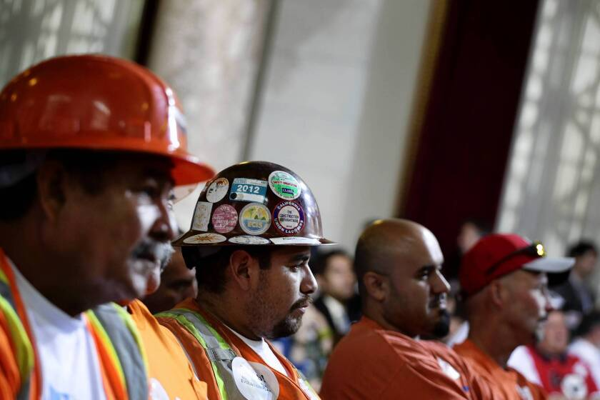 Union member Francisco Gonzalez, center in hard hat with stickers, shows support for a new trash franchise system in the city of Los Angeles.
