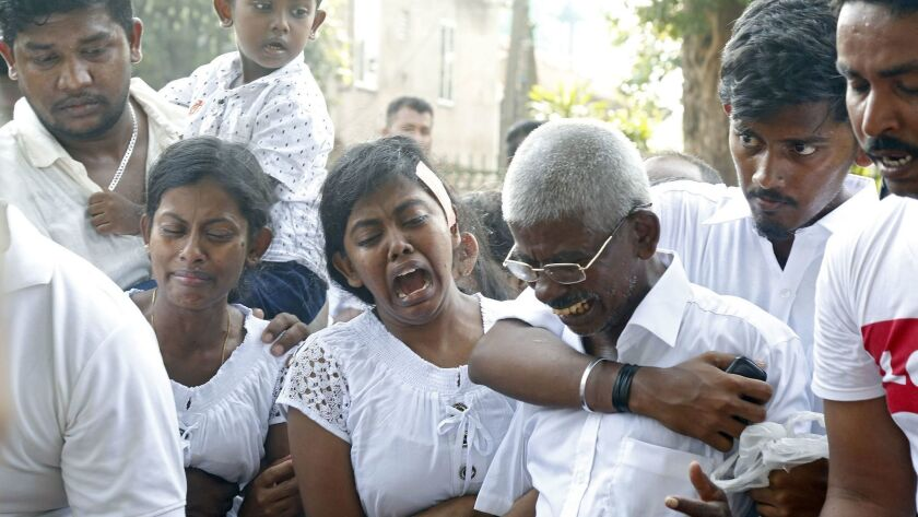 Relatives and friends mourn at Madampe Cemetery in Colombo, Sri Lanka, on Wednesday as they bury victims of Sunday's bomb blasts.