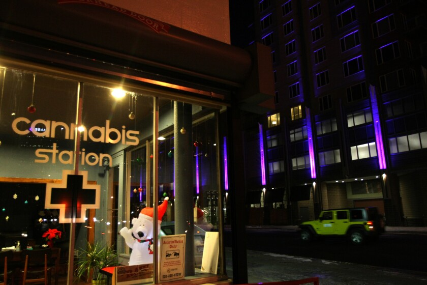 A car passes by the Cannabis Station, a marijuana dispensary in downtown Denver.