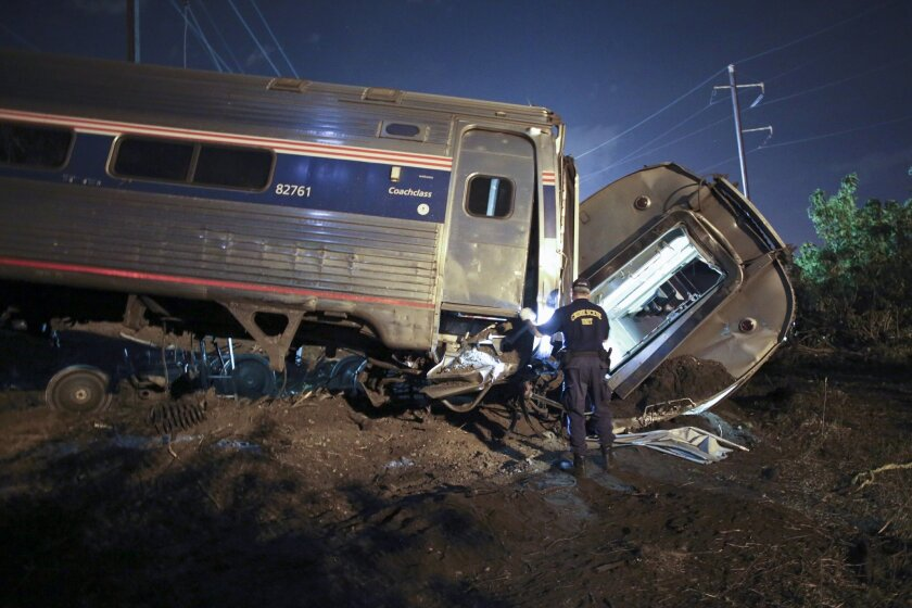 FILE - In this May 12, 2015 file photo, emergency personnel work the scene of a deadly train wreck in Philadelphia. Five years ago, federal safety officials proposed requiring video cameras in train cabs, but it didn't happen. That's left a gap as investigators try to unravel last week's fatal Amtrak derailment. (AP Photo/ Joseph Kaczmarek, File)