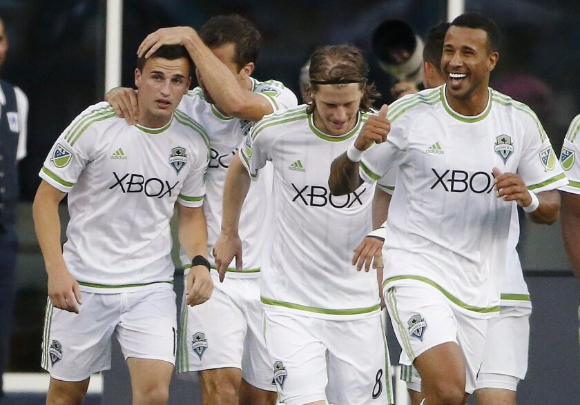 Seattle Sounders's Aaron Kovar, left, celebrates his goal with teammates during the first half of an MLS soccer game against the New England Revolution, Saturday, May 28, 2016, in Foxborough, Mass. (AP Photo/Michael Dwyer)
