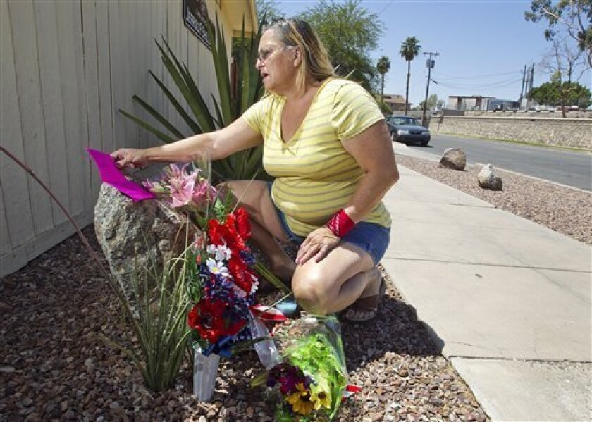 DeAnna Quinto, reads a note she left outside the law office of her friend, attorney Jerrold Shelley, Friday, June 3, 2011 in Yuma, Ariz. Shelley was killed along with four others when Carey Dyess went on a shooting rampage Thursday in Yuma, Wellton and surrounding area. (AP Photo/The Arizona Republic, Tom Tingle) MARICOPA COUNTY OUT; MAGS OUT; NO SALES
