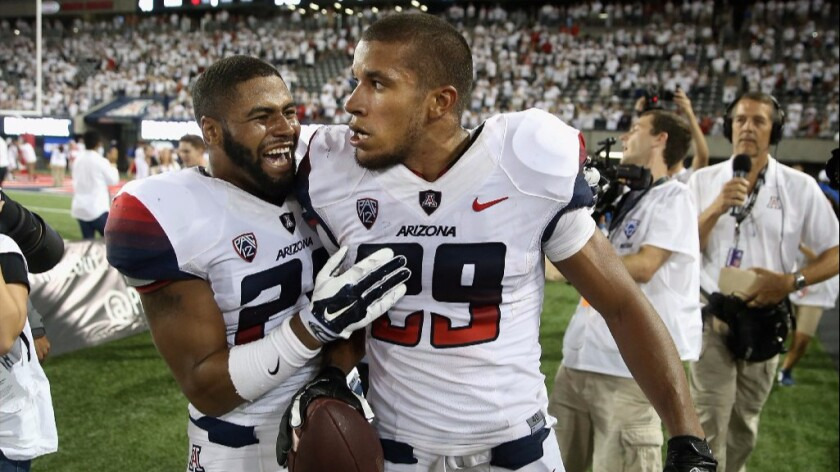 Arizona receiver Austin Hill (29) celebrates with a teammate after catching a game-winning, 47-yard touchdown pass against California on Sept. 20, 2014.