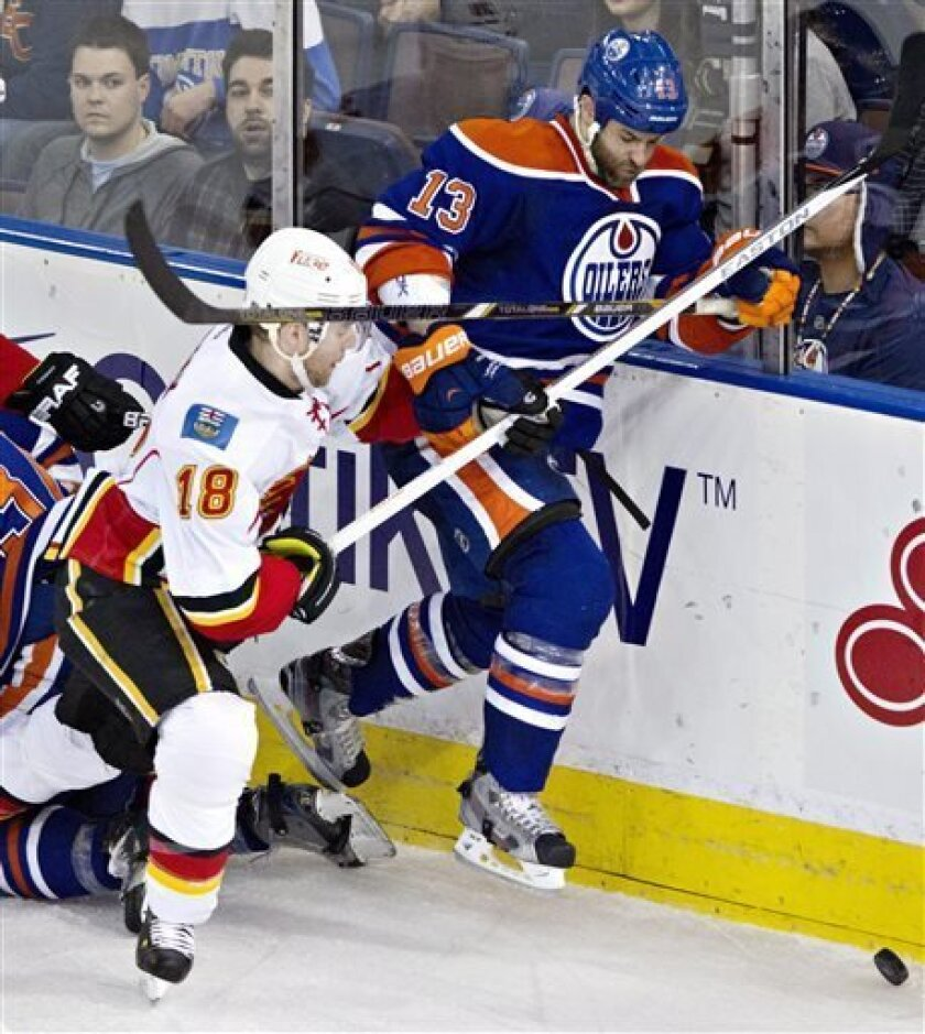 Calgary Flames Matt Stajan (18) checks Edmonton Oilers Mike Brown (13) during second period NHL hockey action in Edmonton, Alberta, on Monday April 1, 2013. (AP Photo/The Canadian Press, Jason Franson).