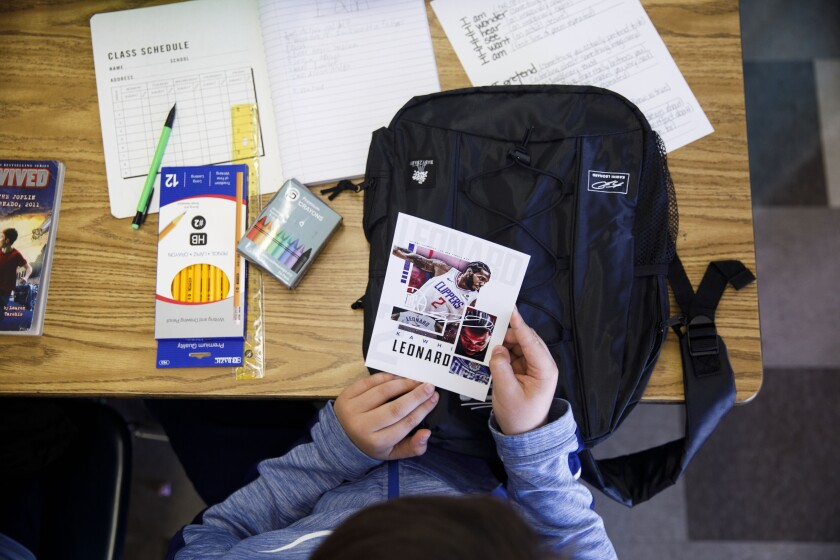 A student looks at a card of Clippers Kawhi Leonard after he gave backpacks away to students at One Hundred Seventh Street Elementary School on Tuesday in the Watts neighborhood of Los Angeles.