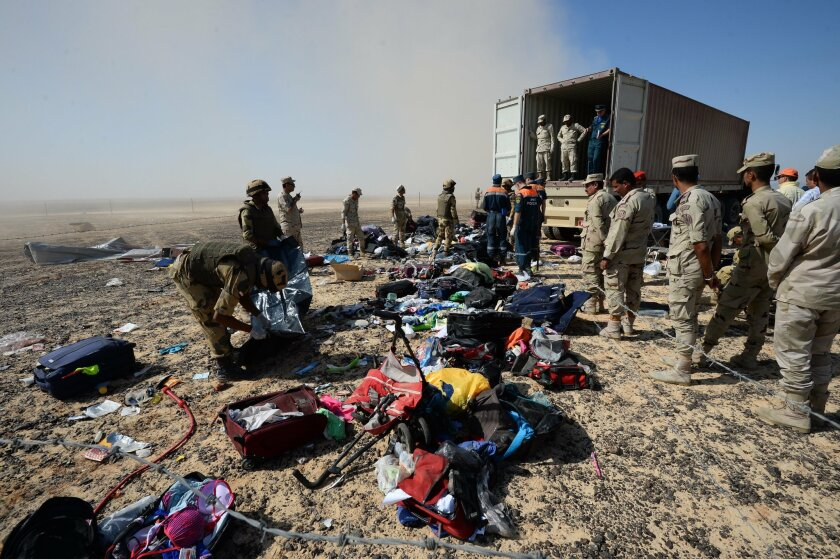 FILE - In this Monday, Nov. 2, 2015 file photo provided by the Russian Ministry for Emergency Situations, Egyptian soldiers collect personal belongings of plane crash victims at the crash site of a passenger plane bound for St. Petersburg in Russia that crashed in Hassana, Egypt's Sinai Peninsula.