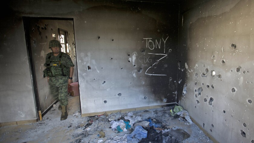 A soldier enters a bullet-riddled home marked with the initials of the Gulf cartel and the Zetas gang in Ciudad Victoria, in Mexico's Tamaulipas state, in September.
