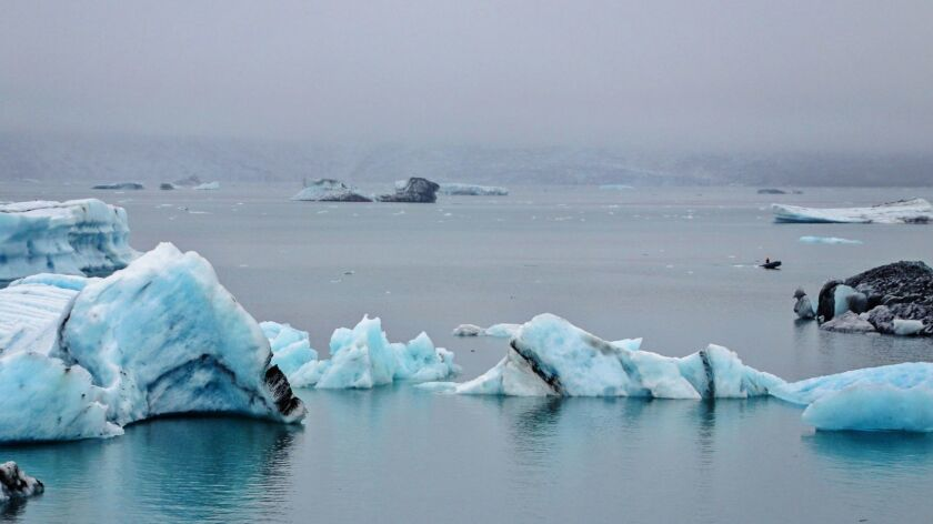 A single small boat flits among the icebergs of Jokulsarlon.