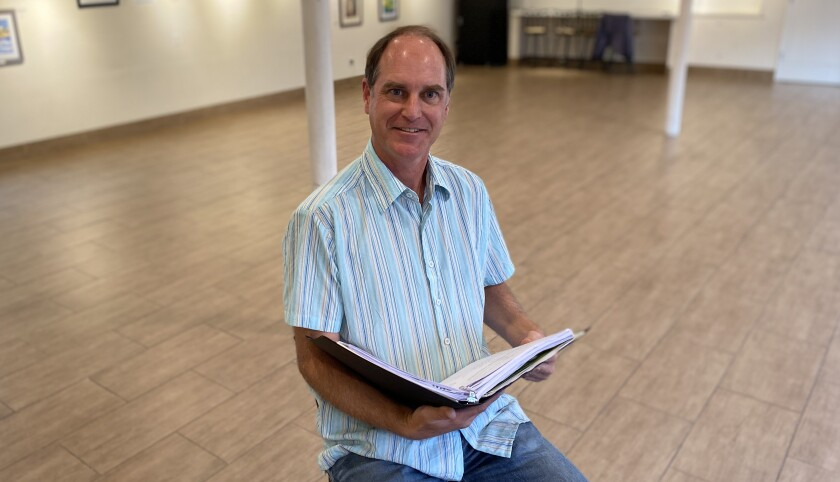 John Tessmer poses in the Great Room at La Jolla Community Center, where he is about to direct and act in a program of a dozen short plays about climate change.