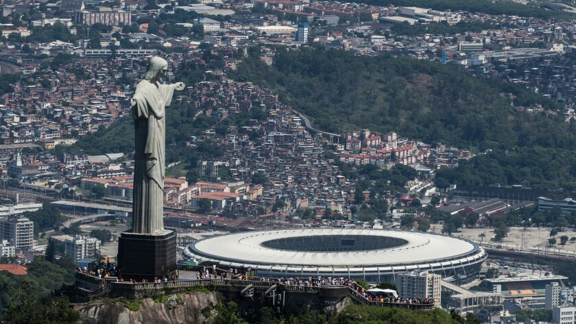 An aerial view of Mario Filho stadium looms beyond the Christ the Redeemer statue atop Corcovado Hill in Rio de Janeiro. The stadium, also known as Maracana stadium, will host the World Cup final and the 2016 Summer Olympics.