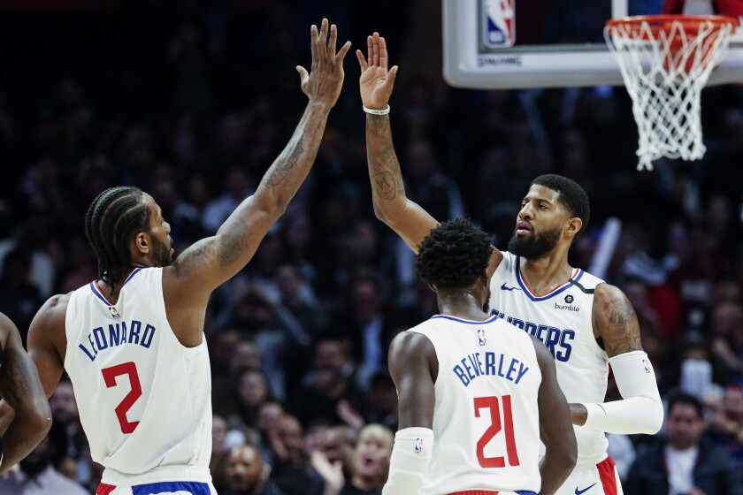 FILE - In this Monday, Feb. 3, 2020, file photo, Los Angeles Clippers' Paul George, right, celebrates with teammate Kawhi Leonard (2) after scoring against the San Antonio Spurs during the second half of an NBA basketball game, in Los Angeles. Leonard and George are healthy at the same time to start the 2020-21 season, and that's given the Clippers a renewed sense of optimism. (AP Photo/Ringo H.W. Chiu, File)