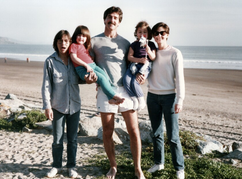 A family poses for a photo on a beach