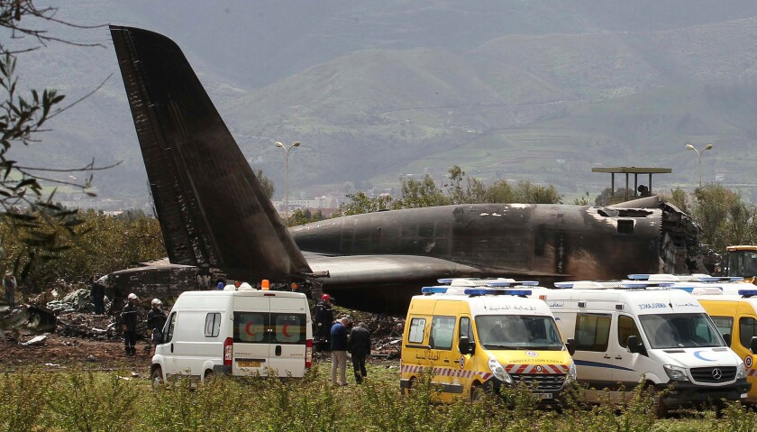 Firefighters and civil security officers work at the scene of a fatal military plane crash in Boufar