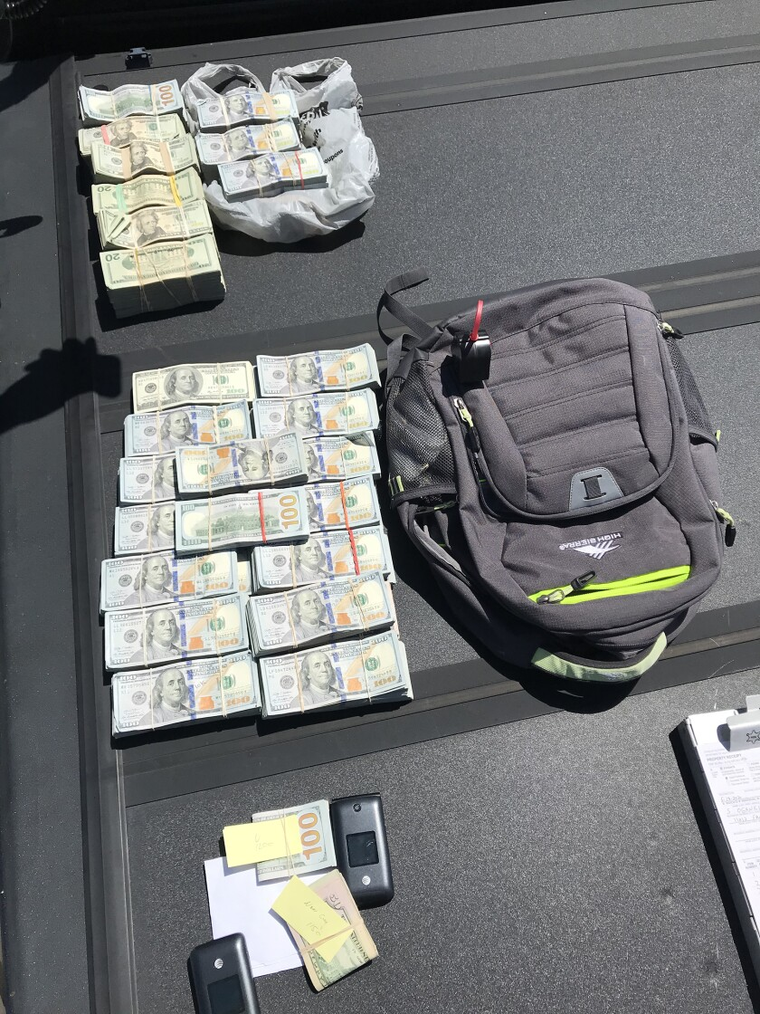 Money, a backpack and other items seized in an Inland Empire drug crackdown.