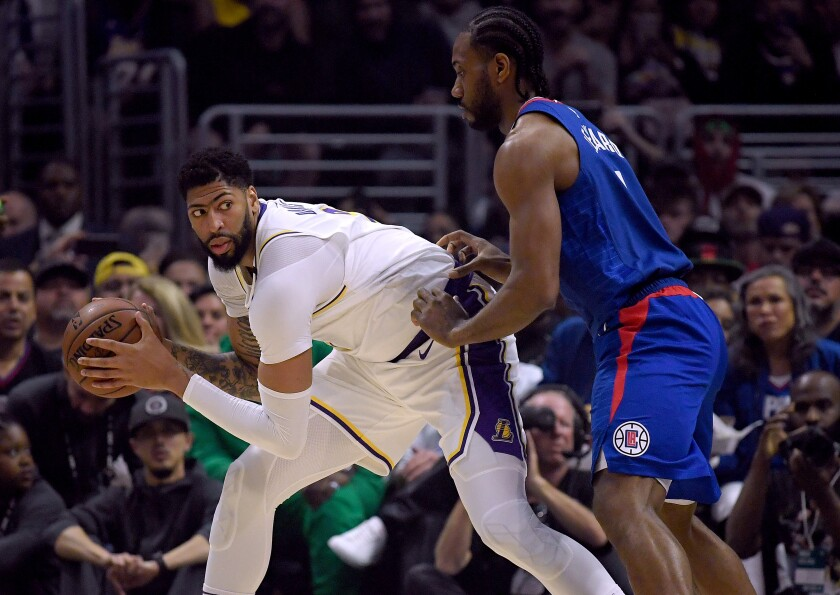 Lakers forward Anthony Davis controls the ball in front of Clippers forward Kawhi Leonard during the Lakers' win at Staples Center on Sunday.