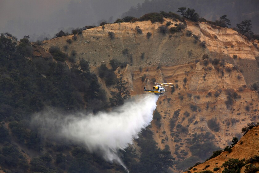 A firefighting helicopter makes a drop on the Grand fire burning in Kern County.