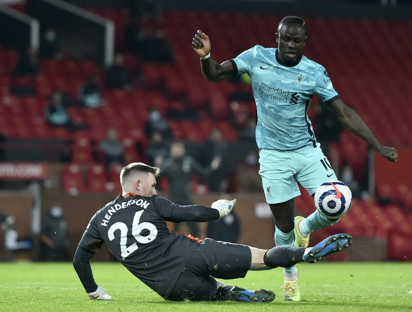 Manchester United's goalkeeper Dean Henderson, left, makes a save in front of Liverpool's Sadio Mane during the English Premier League soccer match between Manchester United and Liverpool, at the Old Trafford stadium in Manchester, England, Thursday, May 13, 2021. (Peter Powell/Pool via AP)