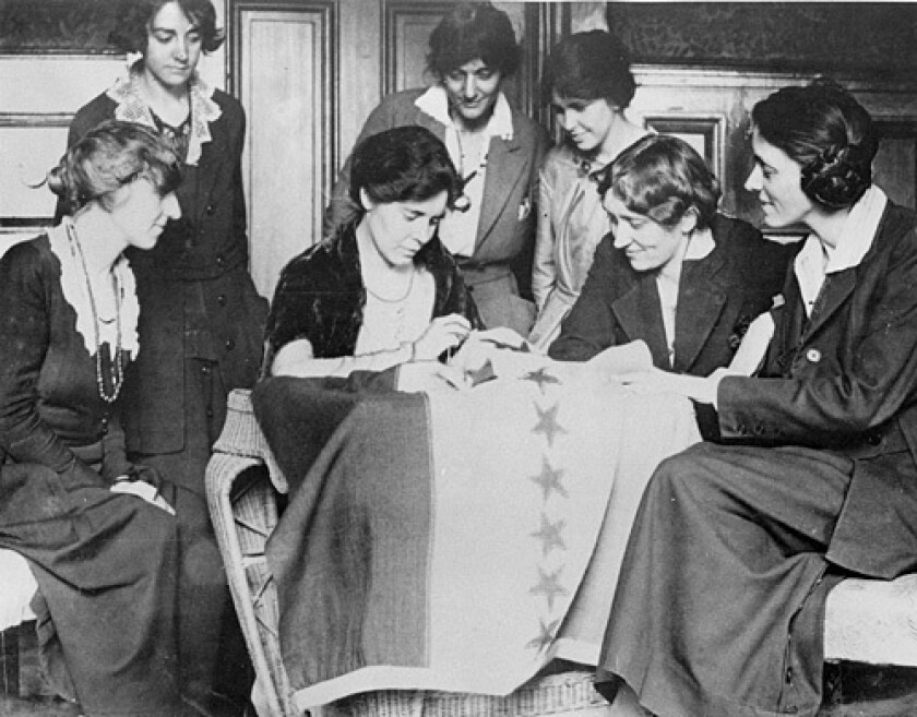 Celebrating ratification of the woman's suffrage amendment, Alice Paul sews a 36th star on a banner in August 1920.