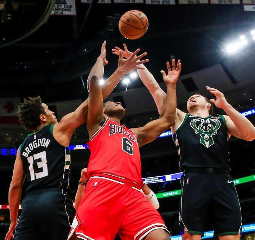 Los escoltas Pat Connaughton (d) y Malcolm Brogdon (i) de Milwaukee Bucks en acción ante el alero brasileño Cristiano Felicio (c) de Chicago Bulls este lunes durante un juego de la NBA entre Chicago Bulls y Milwaukee Bucks, en el United Center de Chicago, Illinois (EE .UU.). EFE
