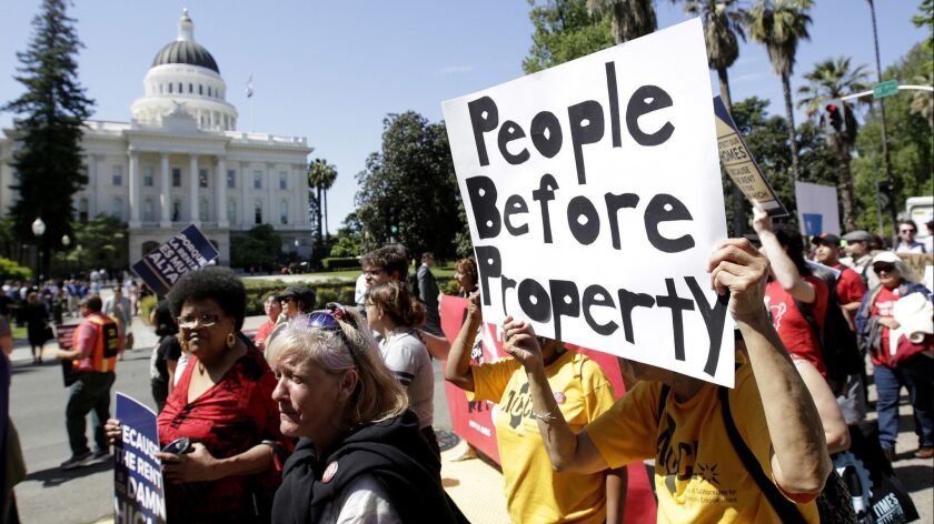 FILE - In this April 23, 2018, file photo rent control supporters march past the Capitol in Sacramen