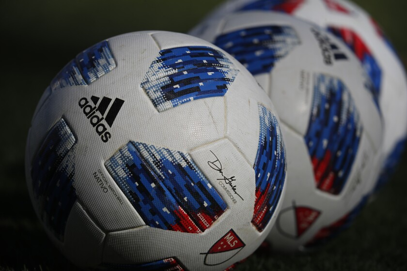 Soccer balls line up in a row.