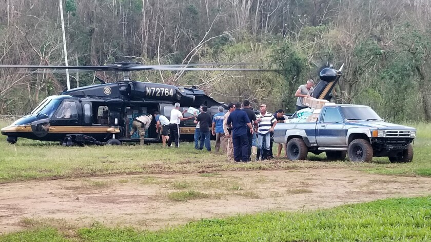 The helicopter bringing aid lands in the mountain community of Casta–er, Puerto Rico.