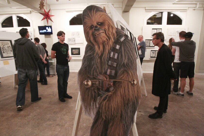 """With a cutout picture of Star Wars character Chewbacca in the foreground, people look at the Star Wars art during the """"The Art of Star Wars"""" exhibit opening at the San Diego Comic Art Gallery on Nov. 21."""