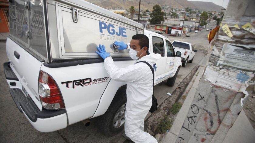 Tijuana, Baja California, MEXICO August 1st, 2017 -- A forensic investigator prepares to review the corner where a taxi driver was gunned down in eastern Tijuana.