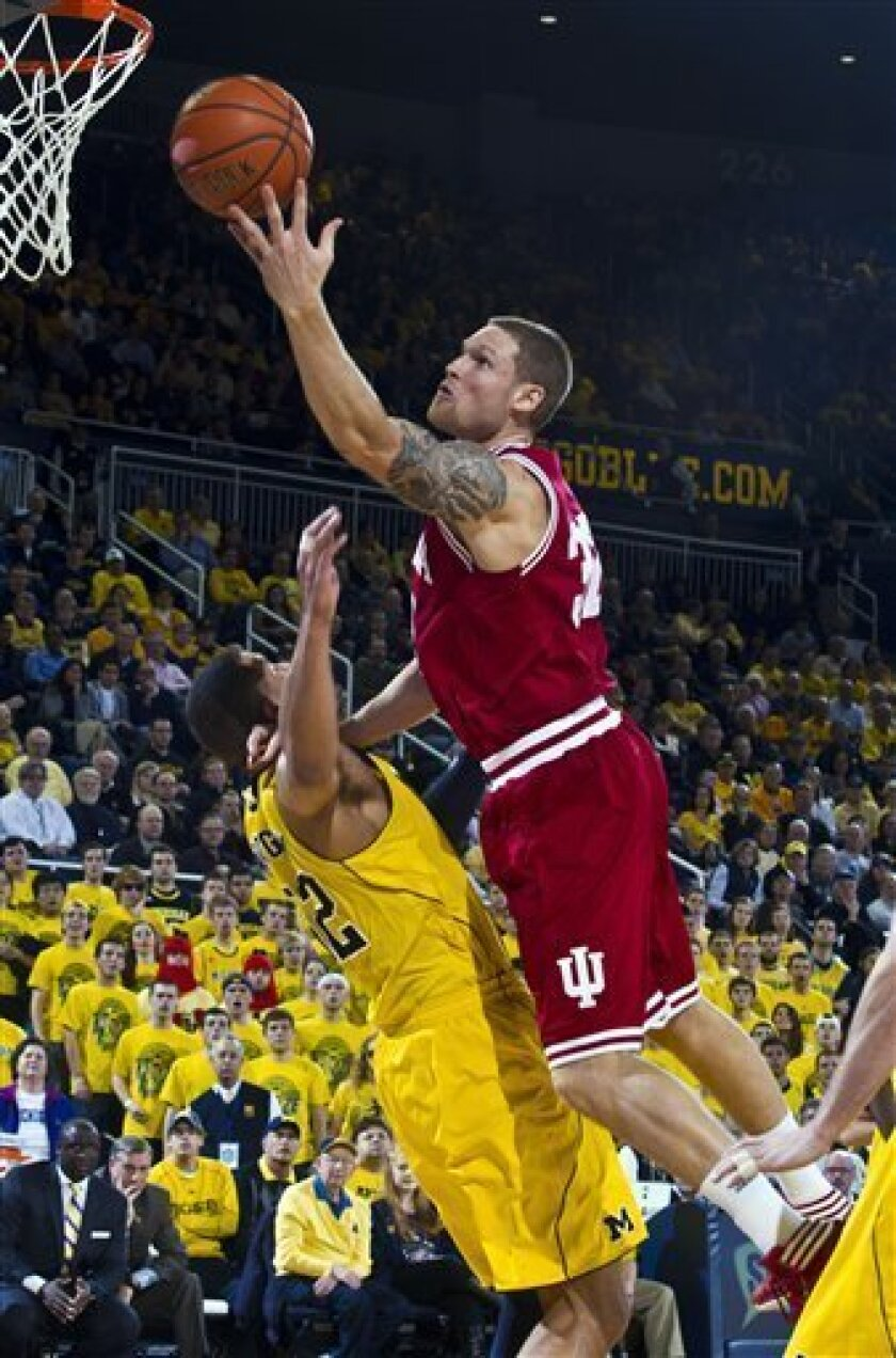 Indiana forward Derek Elston (32) goes to the basket while defended by Michigan forward Jordan Morgan, bottom, in the first half of an NCAA college basketball game, Wednesday, Feb. 1, 2012, in Ann Arbor, Mich. (AP Photo/Tony Ding)