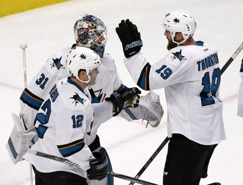 San Jose Sharks goalie Martin Jones (31) celebrates his 2-0 shutout of the Chicago Blackhawks with Patrick Marleau (12) and Joe Thornton after an NHL hockey game Tuesday, Feb. 9, 2016, in Chicago. (AP Photo/Charles Rex Arbogast)