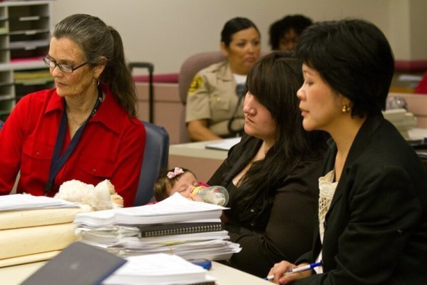 Sabrina Hickman, 18, with her 2-month-old daughter Alauni, is flanked by Victoria Thompson, left, her court appointed special advocate and attorney Ina Tjandrasuwita at Edmund D. Edelman Children's Court in Monterey Park.