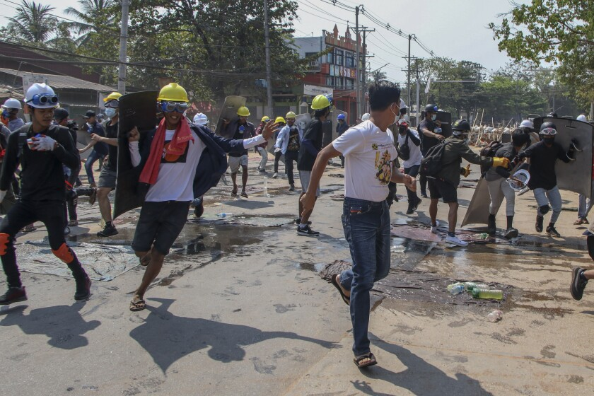 Anti-coup protesters retreat from the frontlines after riot policemen fire sound-bombs and rubber bullets in Yangon, Myanmar, Thursday, March 11, 2021. (AP Photo)