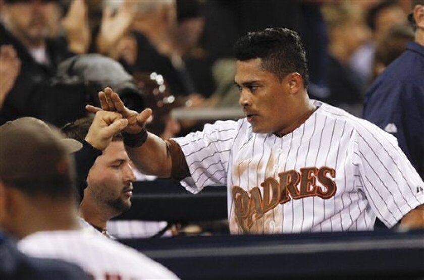 San Diego Padres' Everth Cabrera high fives his way through the dugout after scoring on a sacrifice fly by Chris Denorfia against the New York Mets during the sixth inning of a baseball game Friday, Aug. 3, 2012 in San Diego. (AP Photo/Lenny Ignelzi)