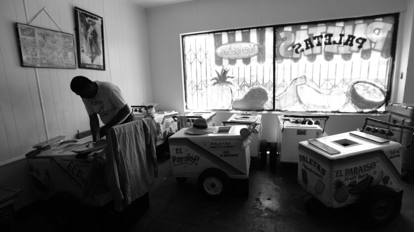 A vendor fills his cart with paletas in the Maravilla neighborhood of East Los Angeles in June. Vendors walk up and down the streets of East L.A. selling the frozen treat.