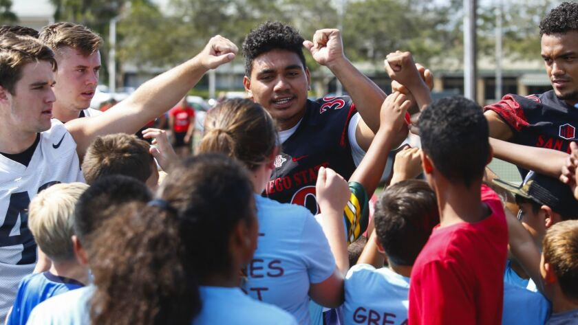 San Diego State linebacker Ronley Lakalaka (center) leads members of the Miramar Boys and Girls Club in a cheer during the Aztecs youth clinic last week at MCAS Miramar.