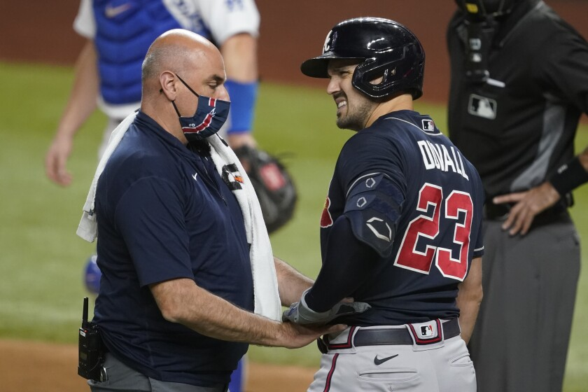 Atlanta Braves' Adam Duvall is checked by a trainer during the second inning in Game 1 of a baseball National League Championship Series against the Los Angeles Dodgers Monday, Oct. 12, 2020, in Arlington, Texas. Duvall left the game. (AP Photo/Tony Gutierrez)