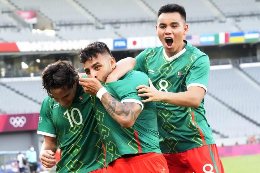 Alexis Vega (centro) celebra con sus compañeros Carlos Rodríguez (derecha) y Diego Lainez