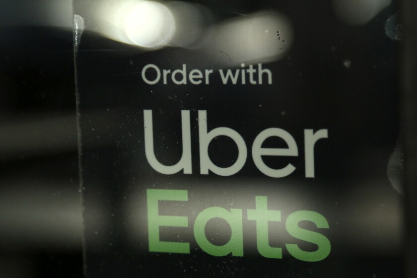 FILE - In this Nov. 6, 2019, file photo, a restaurant advertises Uber Eats in the Coconut Grove neighborhood in Miami. Some app-based delivery companies have announced hiring sprees to cope with a surge in orders from millions of people stuck at home during the coronavirus outbreak. Uber has an internal app that helps its ride-hailing drivers find work for Uber Eats and other jobs. (AP Photo/Lynne Sladky, File)