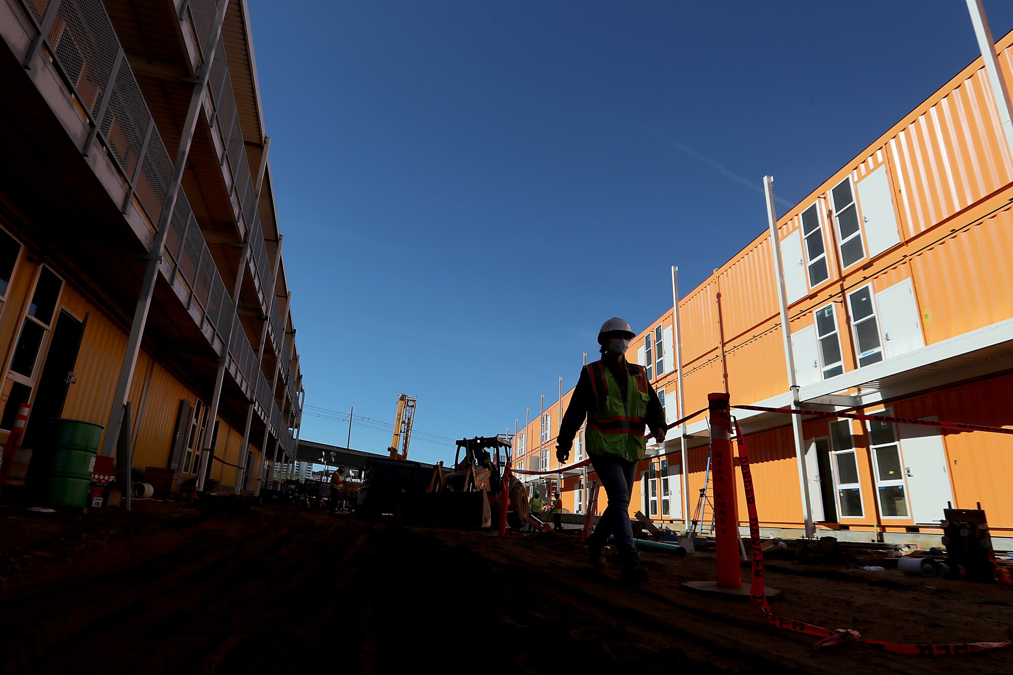 A worker in a hard hat and high-visibility vest walks in between housing built from shipping containers.
