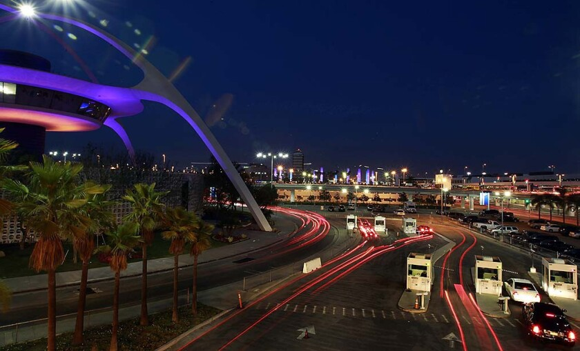 Traffic moves past the Encounters restaurant at LAX. More than a year after airport police began cracking down on ride-hailing services picking up passengers in the terminal area, Los Angeles city officials are pushing regulators to legalize Uber and Lyft.