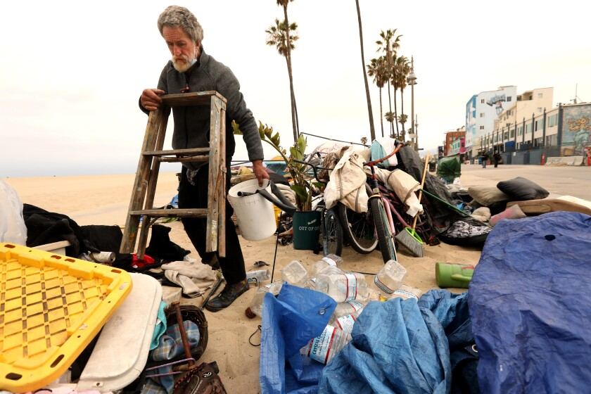 A man gathers belongings at a camp on the beach