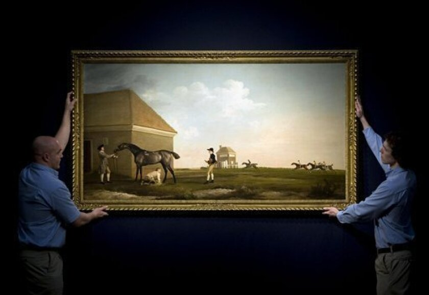 """Christie's employees hang a painting entitled """"Gimcrack On Newmarket Heath, With A Trainer, A Stable-lad, And A Jockey"""" by George Stubbs which is valued at more than 20 million pounds (US$33 million) in London Wednesday April 6, 2011. John Stainton, Christie's senior director of British pictures, said Wednesday that the large portrait measuring more than 6 feet by 3 feet (1.8 meters by 0.9 meters) is """"one of the finest sporting pictures ever painted."""" It will be offered at Christie's in London on July 5. (AP Photo/Anthony Devlin/PA) UNITED KINGDOM OUT NO SALES NO ARCHIVE"""
