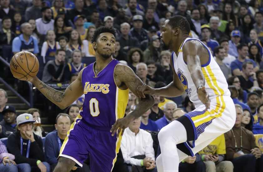 Lakers' Nick Young, left, looks to pass as Golden State Warriors' Kevin Durant defends during the first half of a game on Nov. 23.