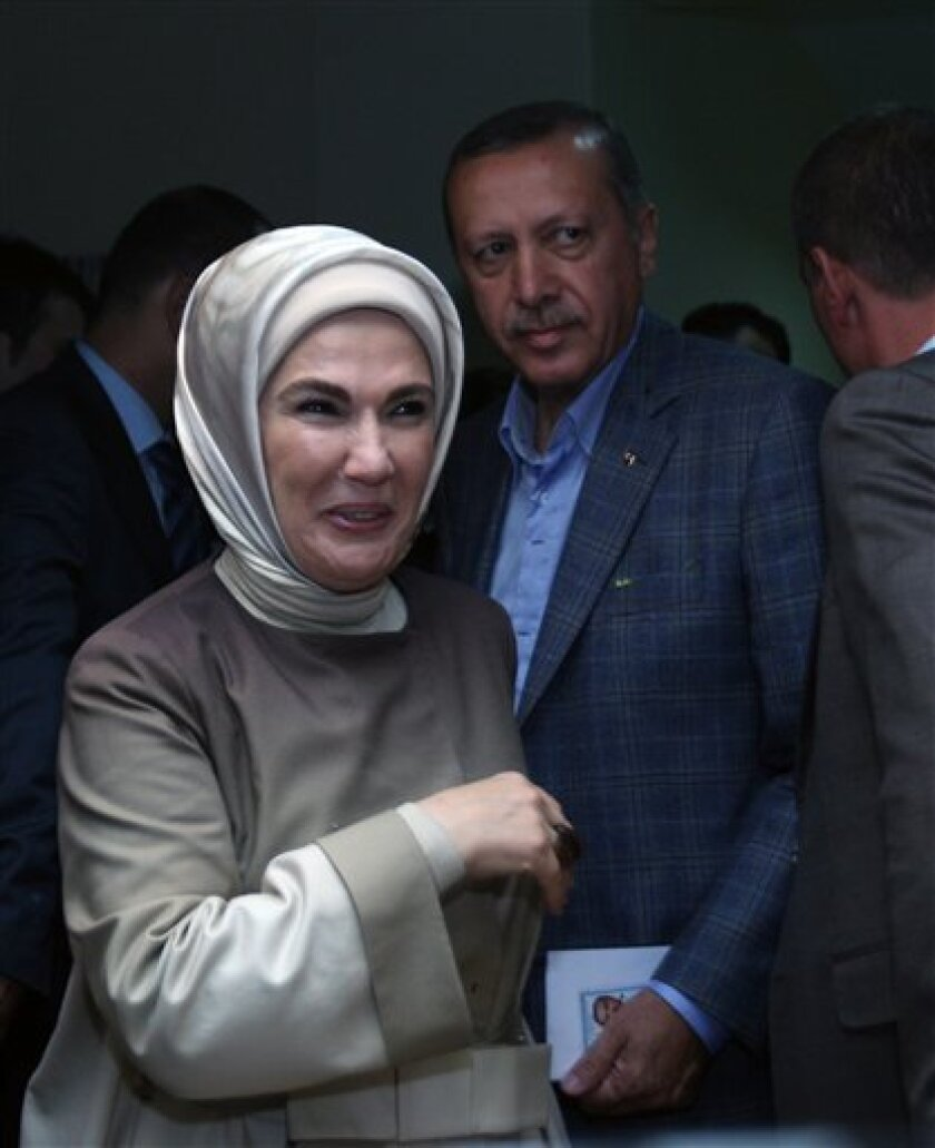 Turkish Prime Minister Recep Tayyip Erdogan, rear, and his wife Emine Erdogan arrive at a polling station to cast their vote in a referendum on changes to the constitution that was crafted in the wake of Turkey's 1980 military coup, In Istanbul, Turkey, Sunday, Sept. 12, 2010. Turks voted Sunday on whether to amend a military-era constitution in what the government says is a key step toward EU-style democracy, despite opposition claims that the proposed reforms would shackle the independence of the courts. The referendum on 26 amendments to a constitution that was crafted after a 1980 military coup has become a battleground between the Islamic-oriented government and traditional power elites that believe Turkey's secular principles are under threat. The outcome will set the stage for elections next year in a strategically located NATO ally whose regional clout has surged in recent years. (AP Photo/Burhan Ozbilici)