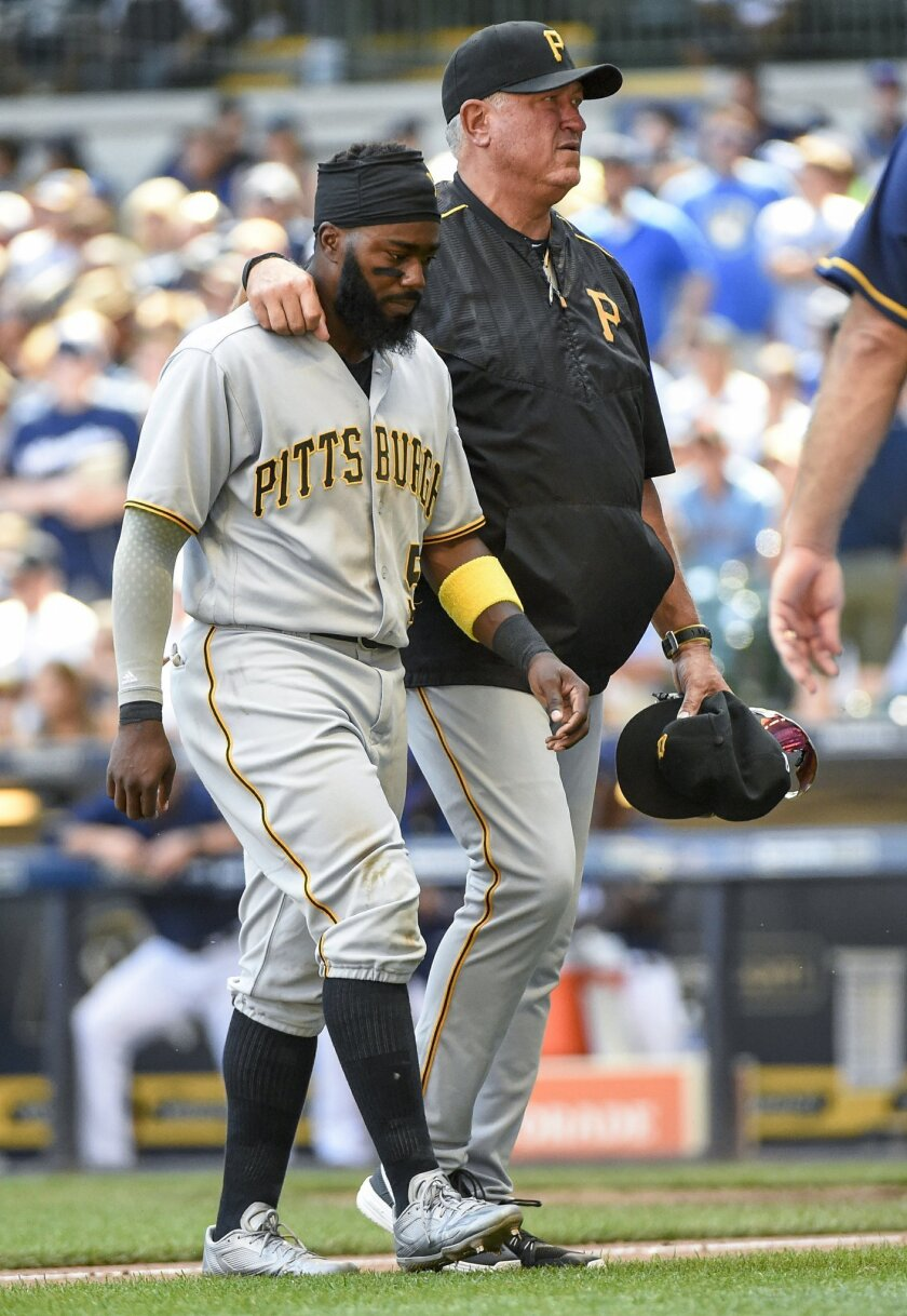 Pittsburgh Pirates' Josh Harrison, left, is helped off the field by manager Clint Hurdle, right, after a collision with Milwaukee Brewers' Keon Broxton during the sixth inning of a baseball game Sunday, July 31, 2016, in Milwaukee. (AP Photo/Benny Sieu)