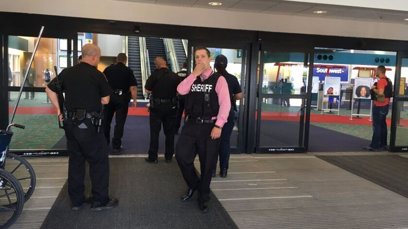 Authorities gather at a terminal at Bishop International Airport in Flint, Mich., where a police officer was attacked by a knife-wielding man Wednesday.