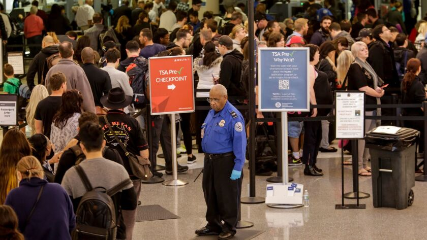 A TSA agent keeps an eye on travelers going through security at Los Angeles International Airport. The ACLU says documents it has obtained do not support the premise of the TSA behavior detection program.