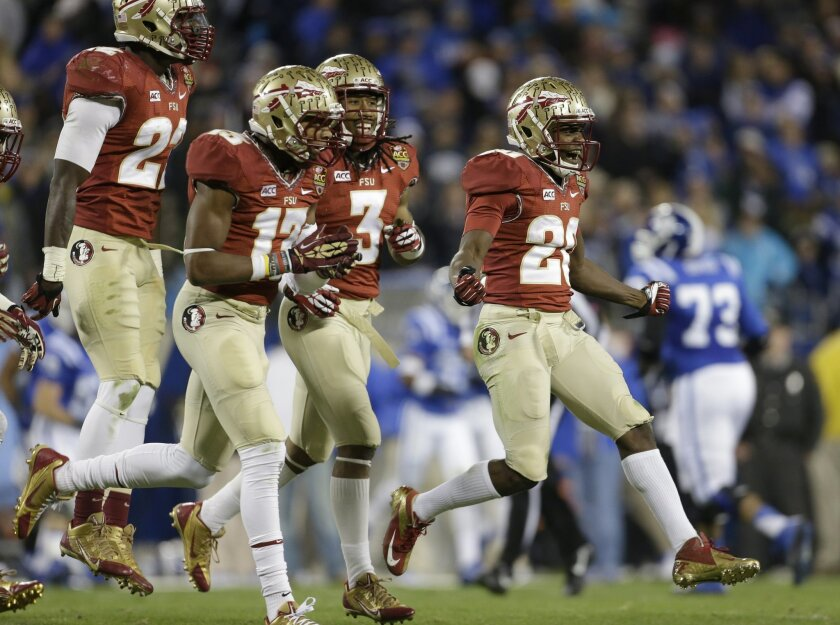 Florida State's Lamarcus Joyner, right, celebrates his interception against Duke with teammates in the first half of the Atlantic Coast Conference Championship NCAA football game in Charlotte, N.C., Saturday, Dec. 7, 2013. (AP Photo/Bob Leverone)