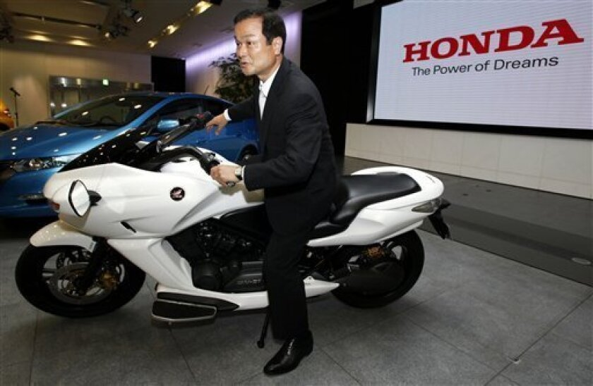 Honda Mortor Co.'s new President Takanobu Ito poses for photos during a press conference at the Honda's headquarters in Tokyo, Japan, Monday, July 13, 2009. Ito is promising to call upon the creative energies of the company founder to ride out hard times. And he's pushing an aggressive strategy built around hybrid green technology. (AP Photo/Junji Kurokawa)