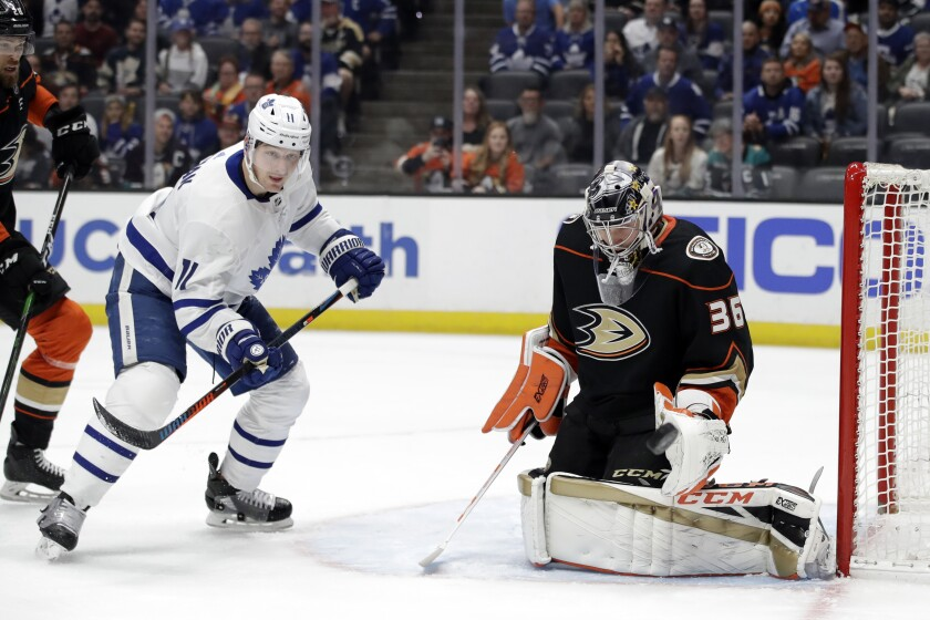Anaheim Ducks goaltender John Gibson, right, stops a shot in front of Toronto Maple Leafs' Zach Hyman during the first period of an NHL hockey game Friday, March 6, 2020, in Anaheim, Calif. (AP Photo/Marcio Jose Sanchez)